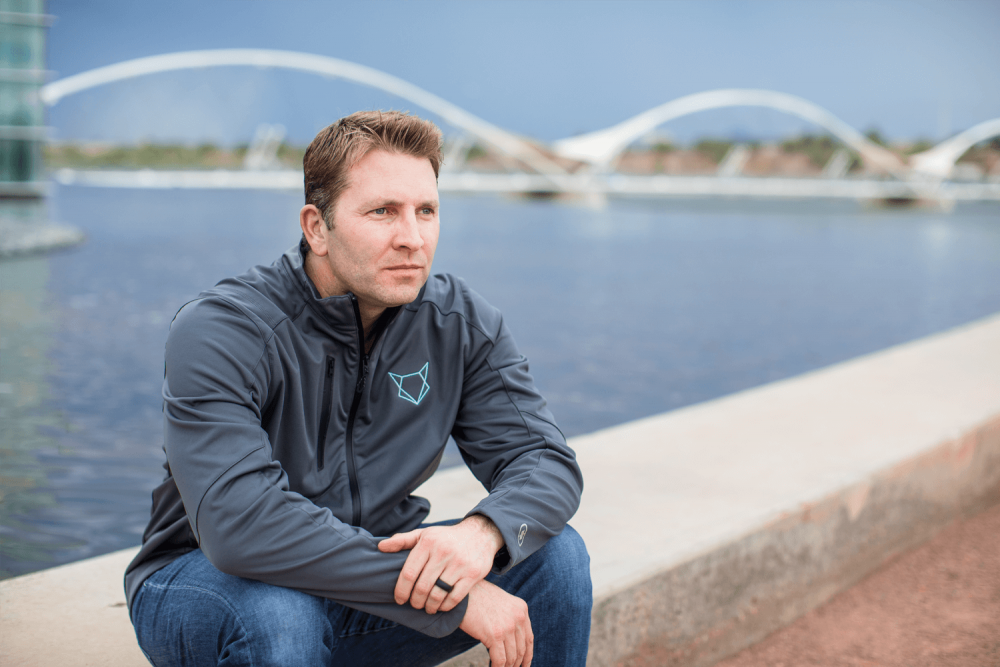 Man sitting on a curb over looking a lake wearing a gray zip up jacket.