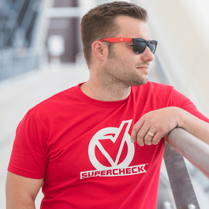 Man wearing red screen print tshirt leaning on rail