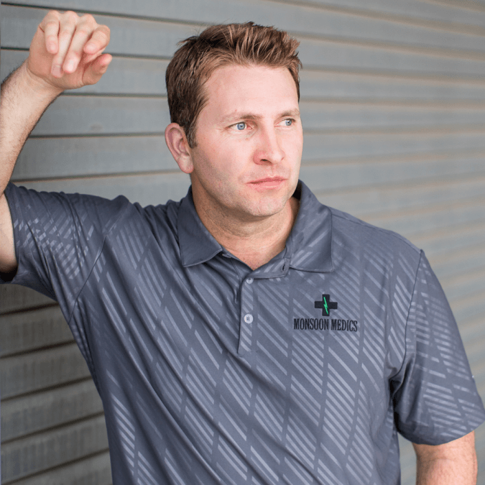 Man leaning against door wearing company branded embroidered polo