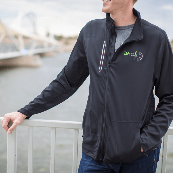 Man leaning against rail wearing black company branded jacket